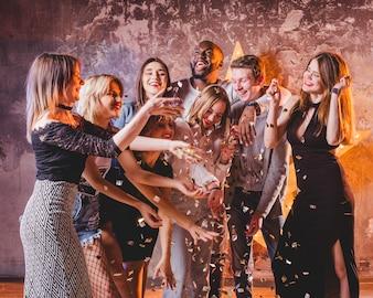 Festive young friends having fun with confetti