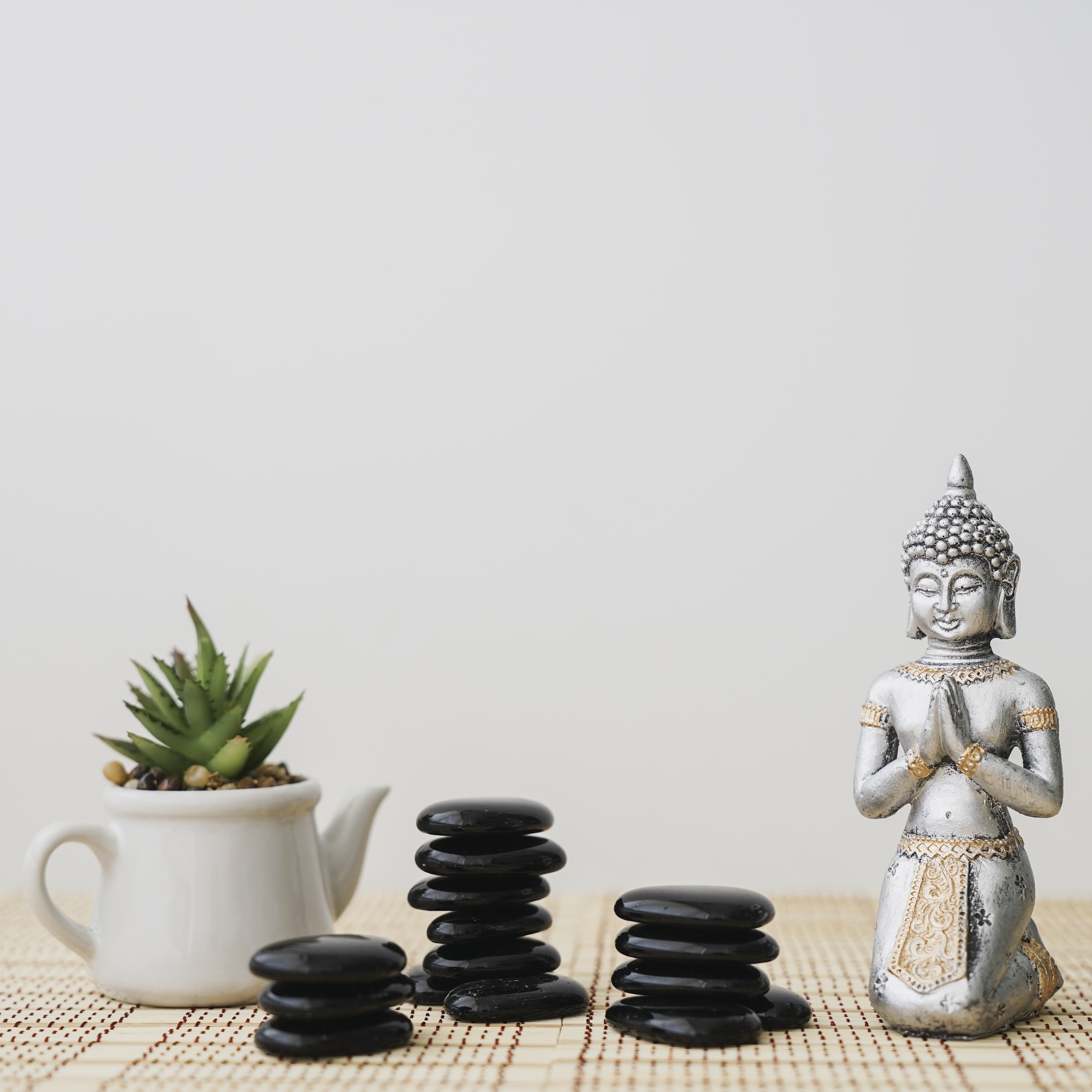 Figure of buddha next to piles of volcanic stones and pot