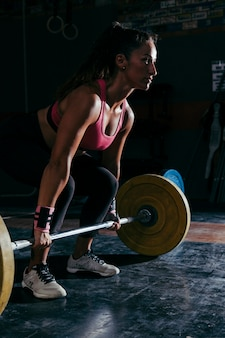 Fitness concept with woman training with barbell