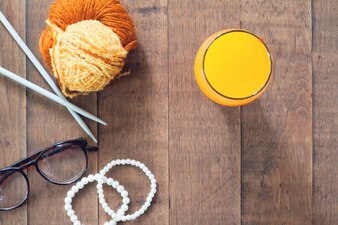 Flat lay of autumn concept with orange juice in glass and woman items