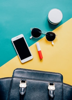 Flat lay of black leather woman bag open out with cosmetics, accessories and smartphone on colorful background