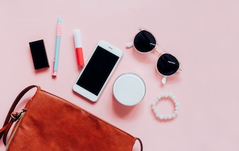 Flat lay of brown leather woman bag open out with cosmetics, accessories and smartphone on pink background with copy space
