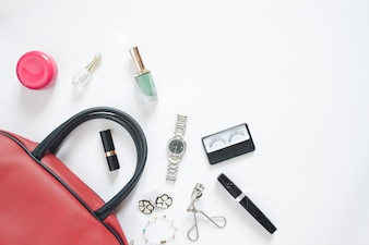 Flat lay of female items out of hand bag on white background