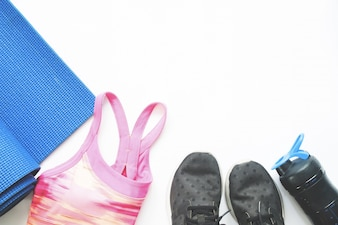 Flat lay of female sport and yoga equipments on white background with copy space