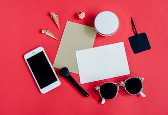 Flat lay of feminine items with cosmetics and accessories with blank card on red background, top view with copy space