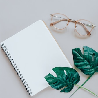 Flat lay of minimal workspace desk with notebook, eyeglasses and green plant, copy space