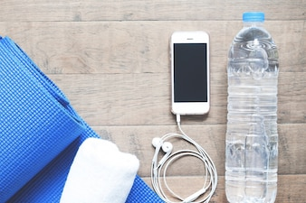 Flat lay of mobile phone with earphones, water bottle, towel and blue yoga mat on wood background. Healthy lifestyle and Yoga, top view
