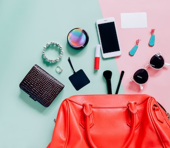 Flat lay of pink cute woman bag open out with cosmetics, accessories, tag card and smartphone on colorful background with copy space