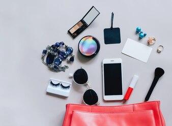 化粧品、アクセサリー、タグカード、スマートフォン、コピースペースのある灰色の背景に開いているピンクのレザーの女性の袋のフラットなレイアウト