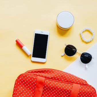 Flat lay of red polka dot woman bag open out with cosmetics, accessories and smartphone on colorful background