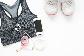 Flat lay of smartphone with measuring tape, sport bra and sport shoes on white background with copy space, Healthy lifestyle and diet concept