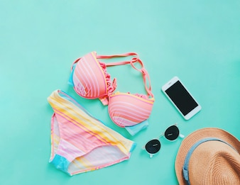 Flat lay of summer items with colorful bikini, sunglasses , hat and smartphone on green background, copy space
