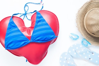 Flat lay of summer travel concept with heart wears bikini with goggles and sandals on white background, Flat lay love vacation