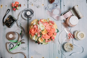 Flatlay of orange wedding bouquet and ribbons on working table