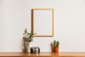 Floral composition with hanging frame and camera