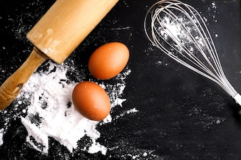 Flour and eggs next to a rolling pin