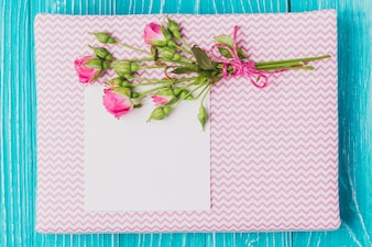 Flowers and piece of paper over book