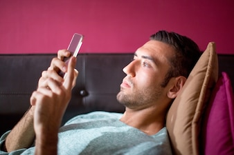 Focused Man Using Smartphone on Sofa in Evening