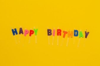 Fondo amarillo con confeti y las letras  happy birthday