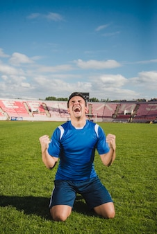 膝の上に目標を祝うサッカー選手