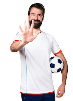 Football player holding a soccer ball counting five