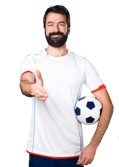 Football player holding a soccer ball making a deal