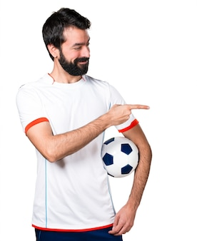 Football player holding a soccer ball pointing to the lateral