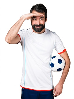 Football player holding a soccer ball showing something