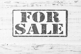 For Sale sign on white wooden background