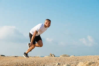 Forceful young athlete starting running outdoors