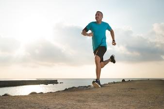 Forceful young man enjoying running outdoors