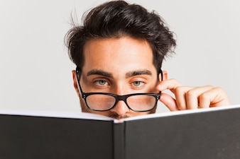 Foreground man with book and glasses