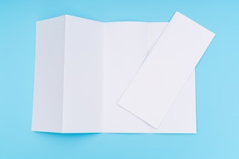 Four- fold white template paper on blue background .