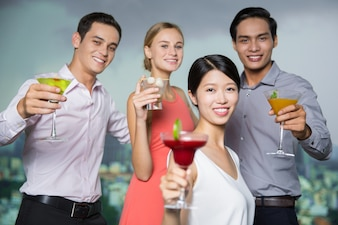 Four Smiling People with Cocktails Toasting in Bar