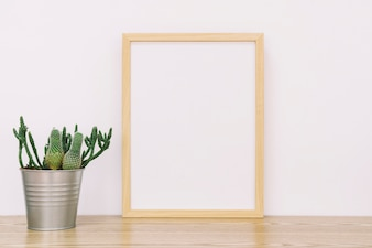 Frame leaning against wall with flower pot
