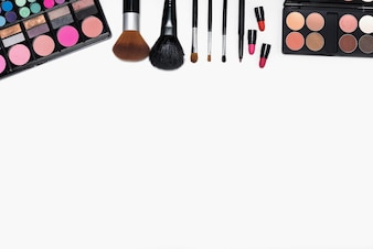 Frame of makeup cosmetics and brushes on white background