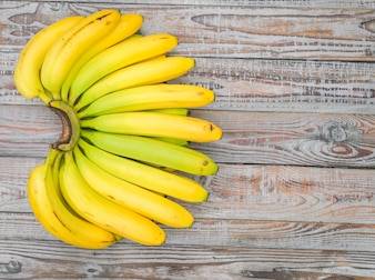 Fresh bananas on wooden table .