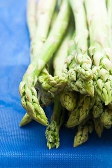 Fresh green asparagus tips on blue background
