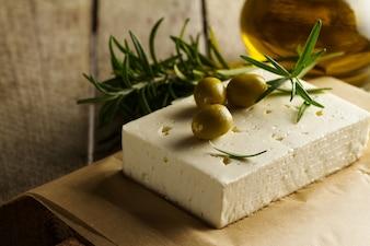 Fresh tasty greek green olives with cheese feta or goat cheese. Closeup. Mediterranean food.