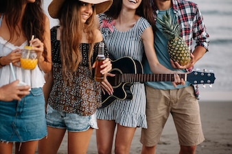 Friends at a beach party with guitar