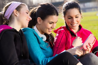 Friends having fun with smartphones after exercise