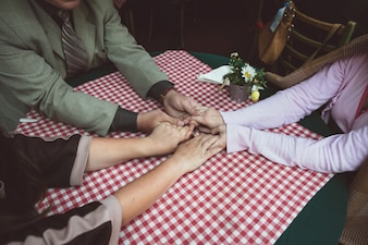 Friends holding hands in a bar