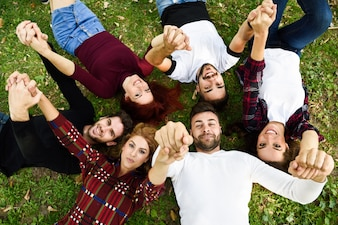 Friends holding hands lying on the lawn of a park