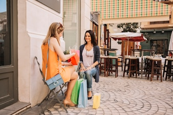 Friends in coffee shop with shopping bags