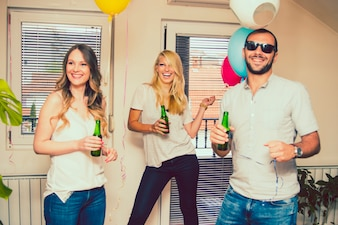 Friends laughing at party with bottle of beer
