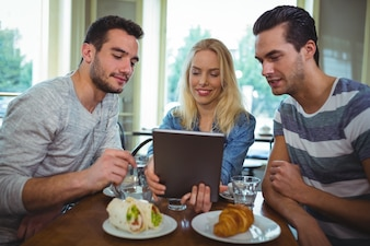 Friends sitting at table and using digital tablet in café