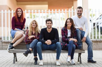 Friends sitting on a wooden bench in the street