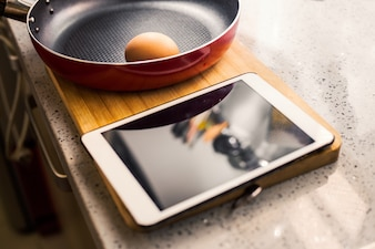 Frying pan with egg and a tablet