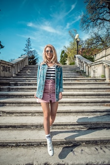 Full length portrait of beautiful fashion model posing on stairs wearing pink skirt and denim jacket