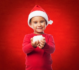 Funny child with snow in hands